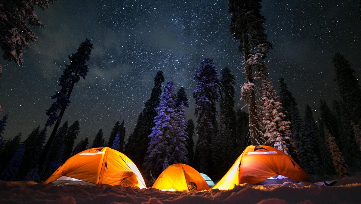 Kempování v přírodě ve stanu pod noční oblohou.
